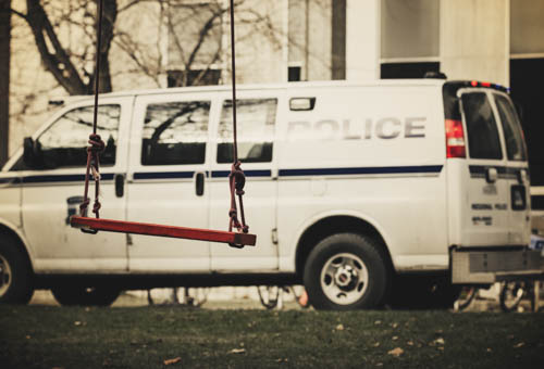 empty swing in front of a police van