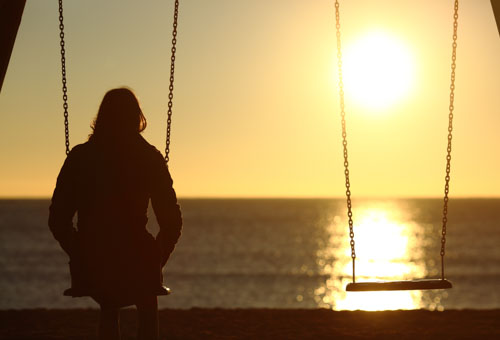 Lonely woman watching sunset alone