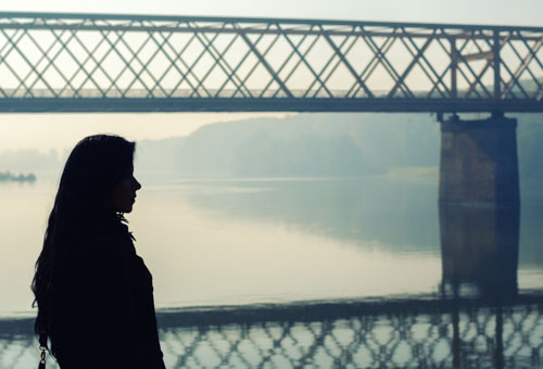 Silhouette of beautiful girl and bridge in autumn